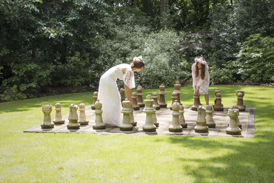 Bride and bridesmaid playing giant chess at Hemsted Location House & Gardens in Benenden