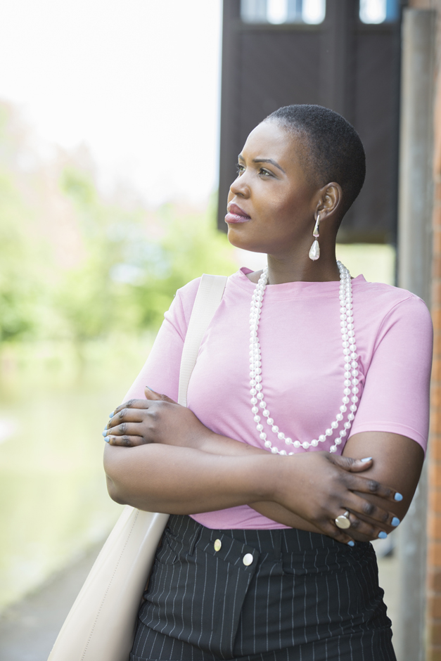 Black business woman with arms crossed looking thoughtfully to the side captured by Kent photographer Victoria Green
