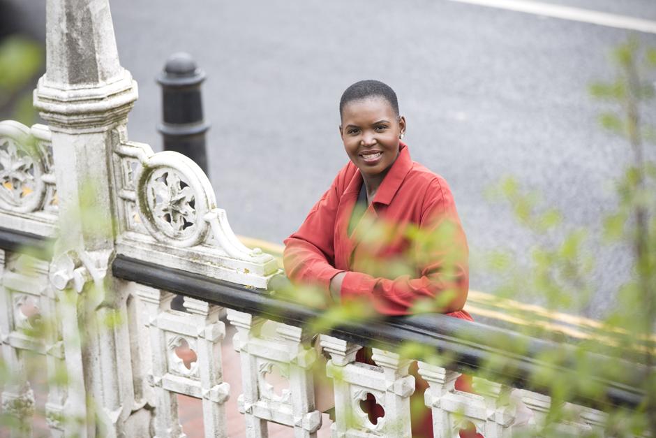 Black businesswoman standing on Tonbridge highstreet bridge captured by Kent photographer Victoria Green