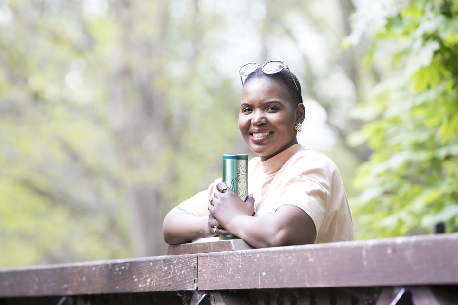 Black woman looking out over the bridge by Tonbridge public swimming pool holding a Starbucks thermos captured by Kent photographer Victoria Green