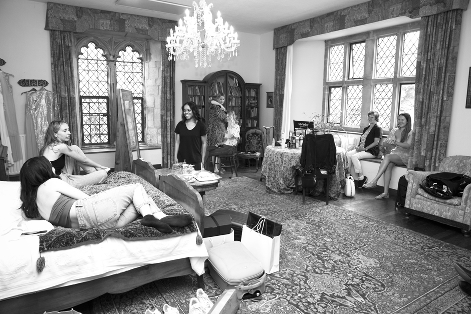 Wide scene of bridal preparation - bridesmaids, bride and mum chatting and laughing - at Nettlestead Place, Maidstone.