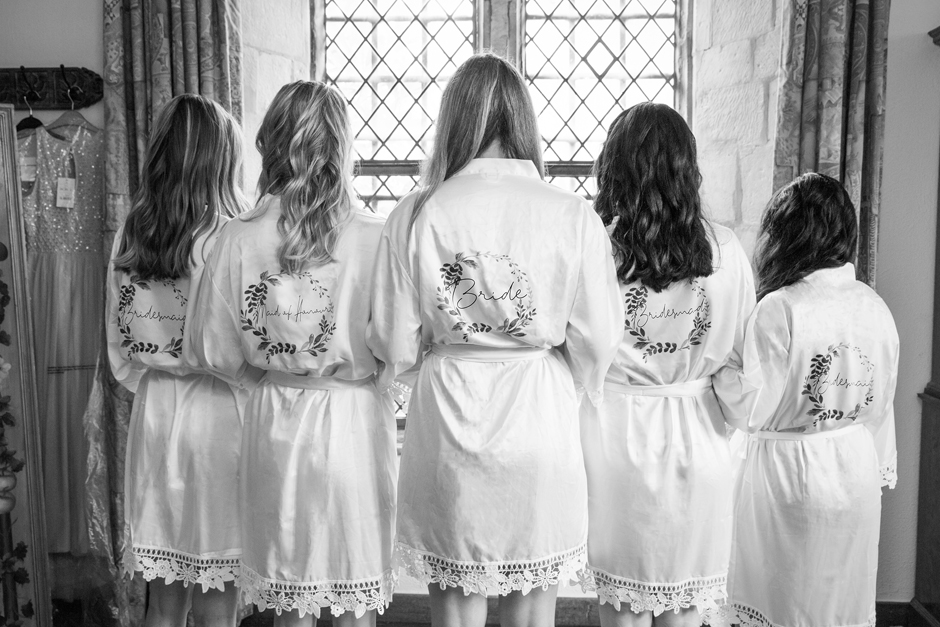 Backs of bride and bridesmaids showing their silk robes with personalised wedding roles. Captured at Nettlestead Place bridal suite by Kent photographer Victoria Green.