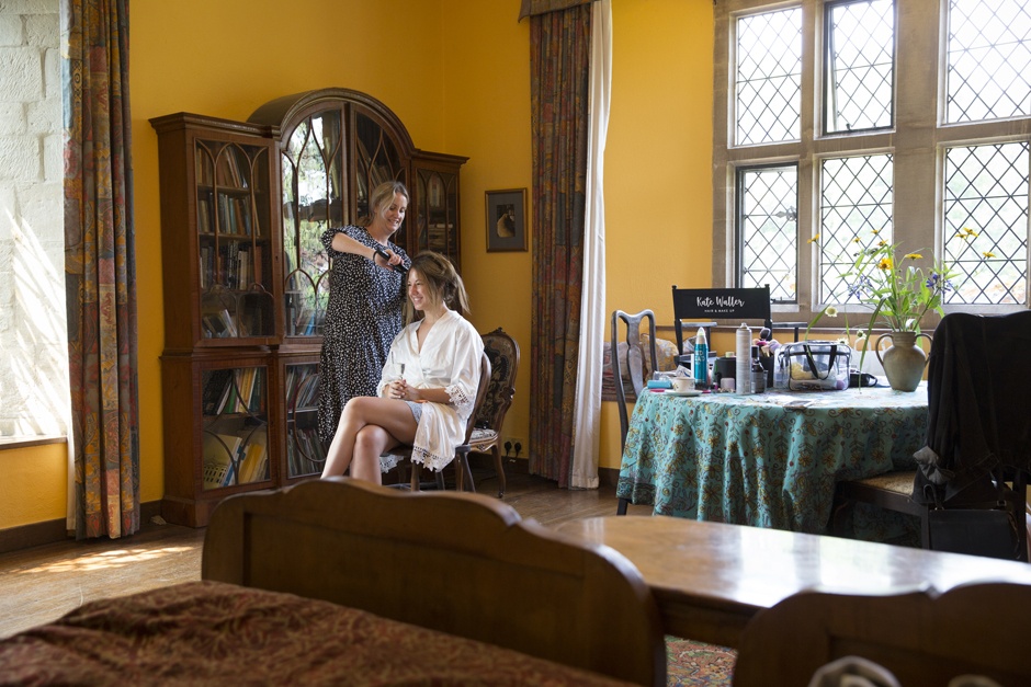 Wide shot of bride having her hair straightened by hairdresser, showing the bridal suite at Nettlestead Place, Kent.