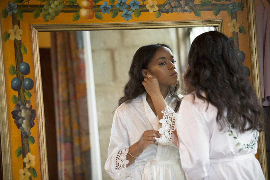 Bridemaid looking in mirror putting her earrings on. Taken at Nettlestead Place by wedding photographer, Victoria Green.