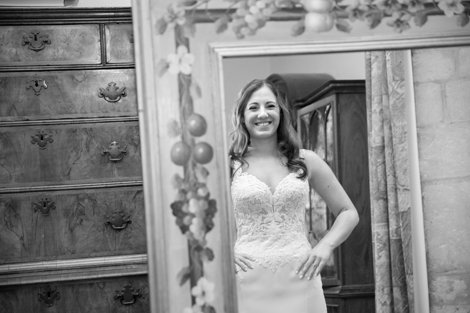 Bride with massive smile looking in mirror at Nettlestead Place captured by Kent wedding photographer Victoria Green.