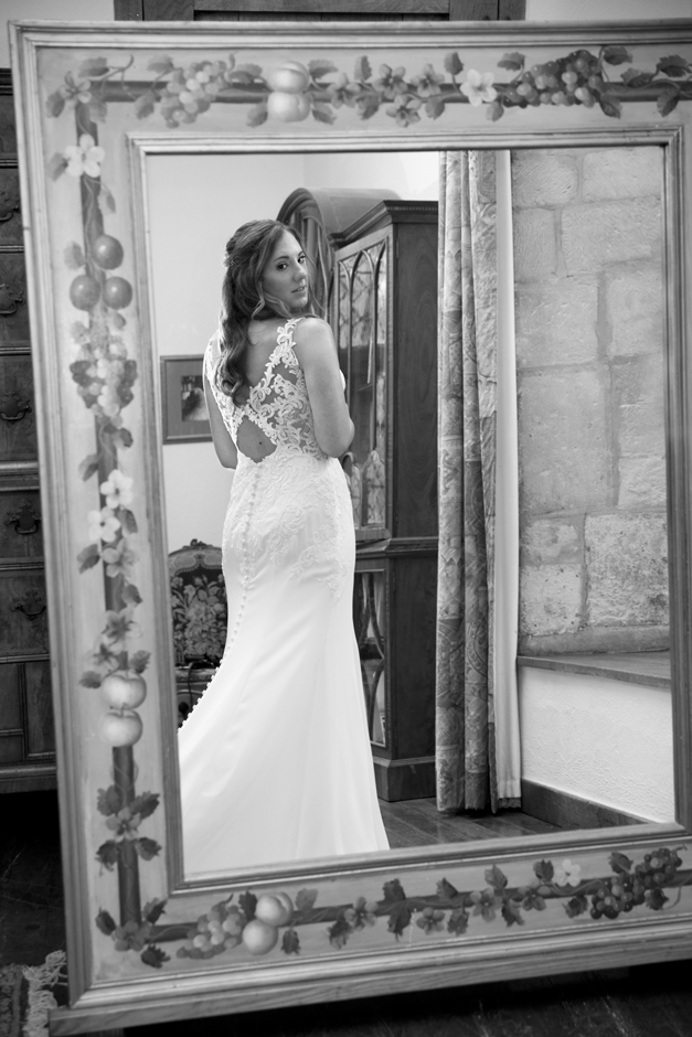 Bride looking at her full length reflection in a mirror at Nettlestead Place. Captured by Kent wedding photographer, Victoria Green.