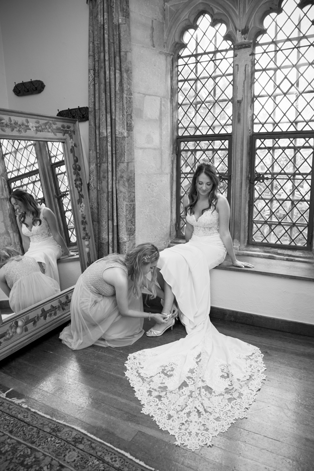Bride having her dress fastened by bridesmaid at Nettlestead Place. Captured by Kent wedding photographer, Victoria Green.