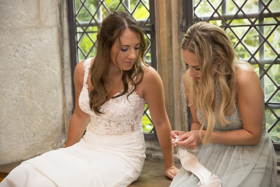 Bride and bridesmaid fixing shoe strap by the window at Nettlestead Place, Kent. Captured by wedding photographer Victoria Green.