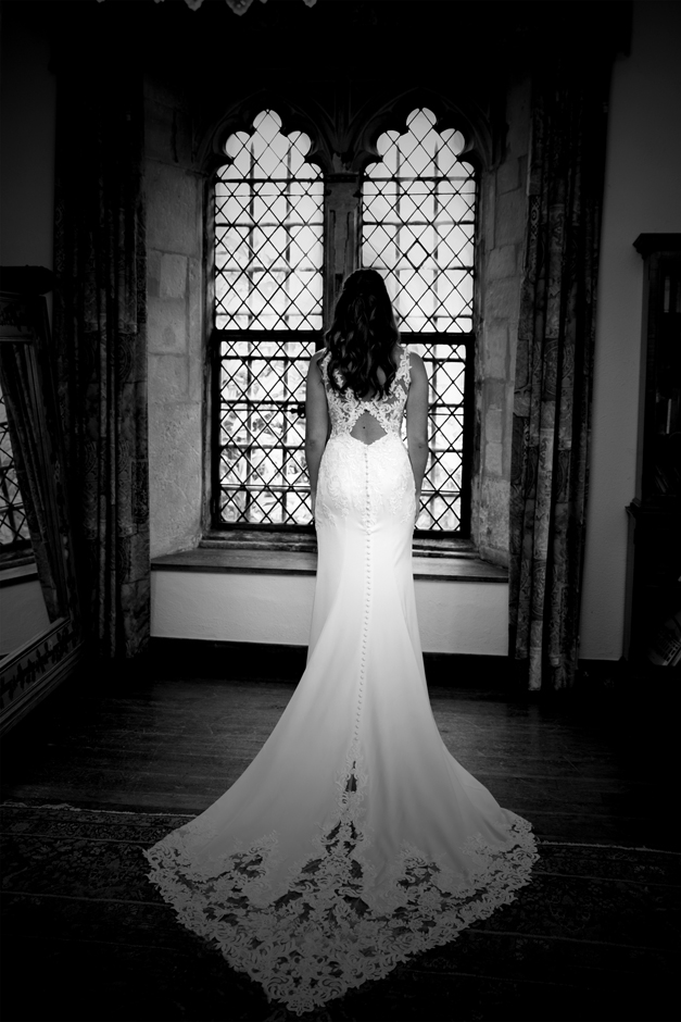 Full length of back of dress as bride looks out of the window at Nettlestead Place wedding. Captured by Kent wedding photographer Victoria Green.