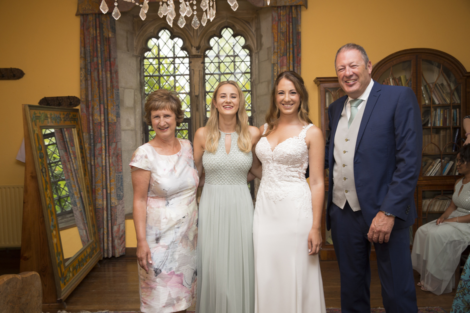 Bride with mum, sister and dad in Nettlestead Place bridal suite before ceremony. Captured by photographer Victoria Green.