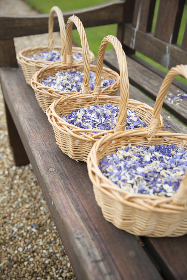 Purple dried confetti petals in wooden baskets at Nettlestead Place, Kent. Captured by photographer Victoria Green.