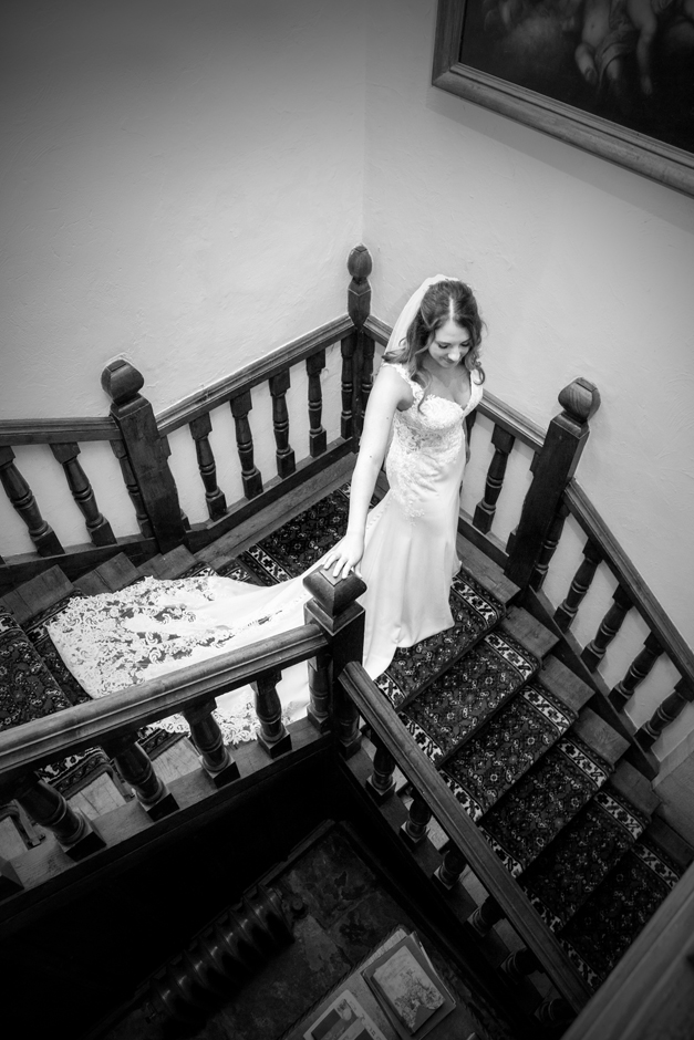 Bride walking down staircase at Nettlestead Place wedding. Captured by photographer Victoria Green.