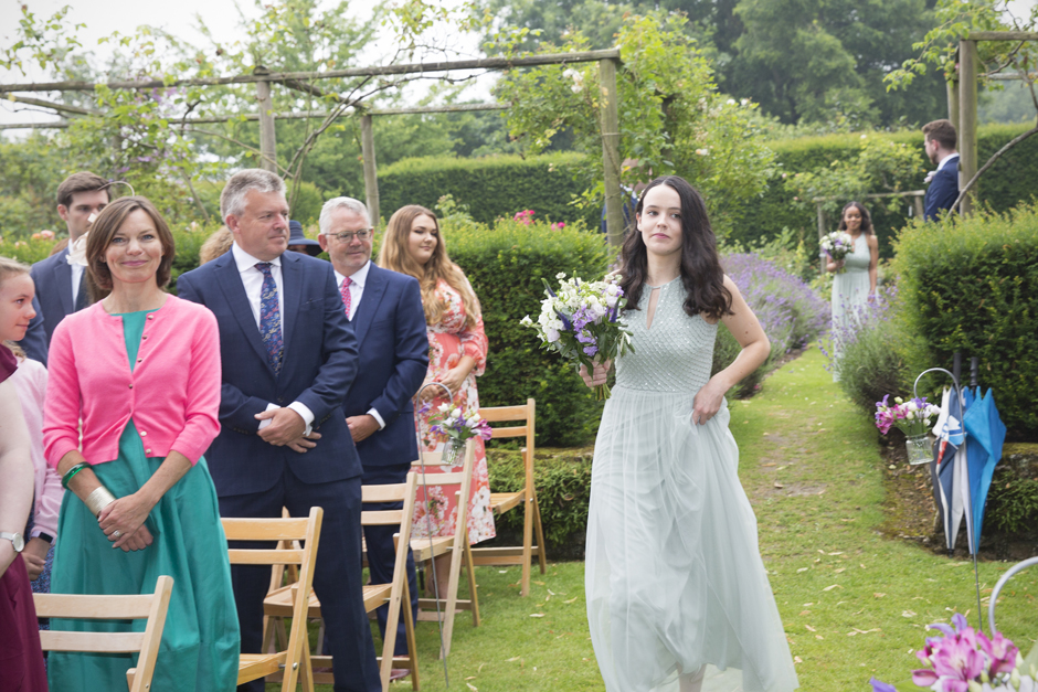 Bridesmaid with black hair walking down the aisle at Nettlestead Place outside ceremony. Captured by photographer Victoria Green.