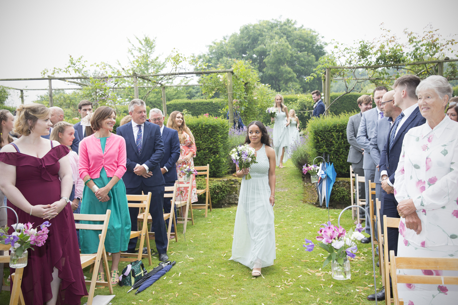 Black bridesmaid walking down the aisle at outdoor wedding ceremony at Nettlestead Place.