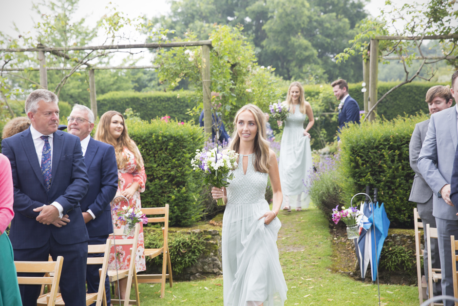 Bridesmaid with blond hair walking down the aisle at outside wedding ceremony at Nettlestead Place, Kent.