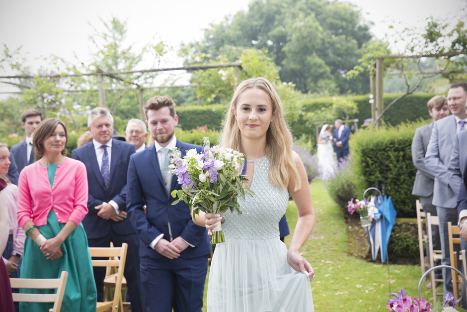 Maid of honour walking down the aisle at outside wedding ceremony at Nettlestead Place, Kent.