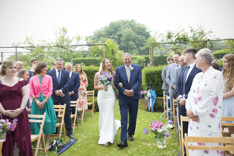 Bride and bride's dad laughing walking down the aisle at outside wedding ceremony at Nettlestead Place. Captured by Kent wedding photographer, Victoria Green.