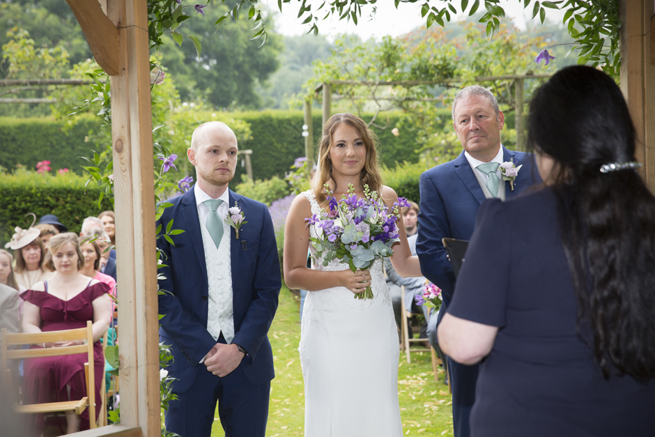 Bride, groom and bride's dad standing at the wooden pergola in line listening to Celebrant at Nettlestead Place.