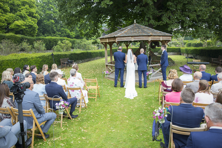 Outside wedding ceremony at Nettlestead Place with guests watching back of bride, bride's father and groom in front of wooden gazebo.