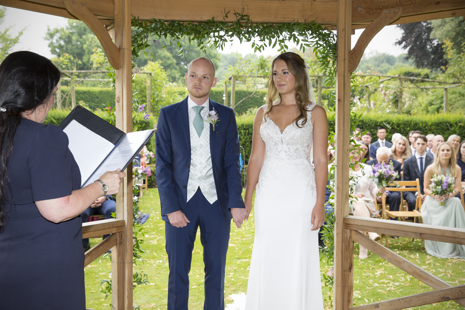 Bride and groom holding hands standing inside wooden gazebo listening to registrar. Outside wedding ceremony captured at Nettlestead Place by photographer Victoria Green.