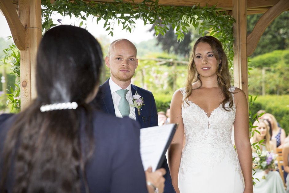 Close-up of bride and groom at outside wedding ceremony at Nettlestead Place, standing under the wooden gazebo and listening to Celebrant. Captured by Kent wedding photographer Victoria Green.