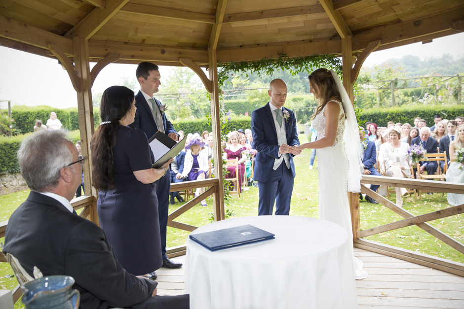 Bride and groom exchanging rings at outside wedding ceremony at Nettlestead Place. Standing under the wooden gazebo as guests look on. Captured by Kent photographer, Victoria Green.