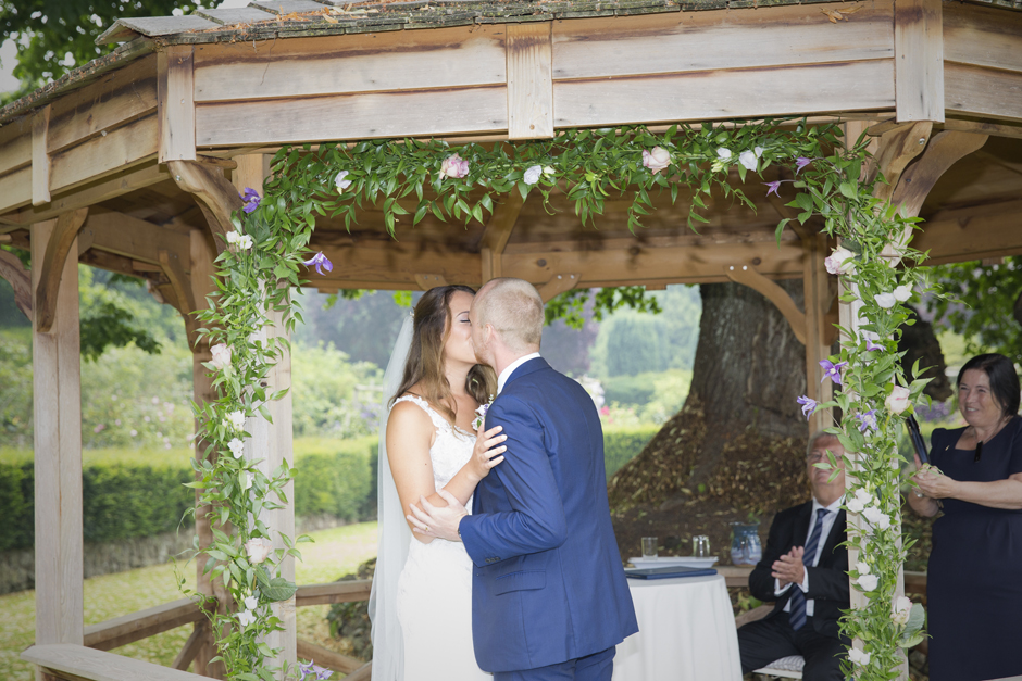 Bride and groom kissing under the wooden pergola at Nettlestead Place outside wedding ceremony. Captured by Kent wedding photographer Victoria Green.