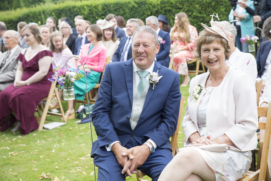 Bride's parents laughing at outside ceremony at Nettlestead Place, Maidstone in Kent.