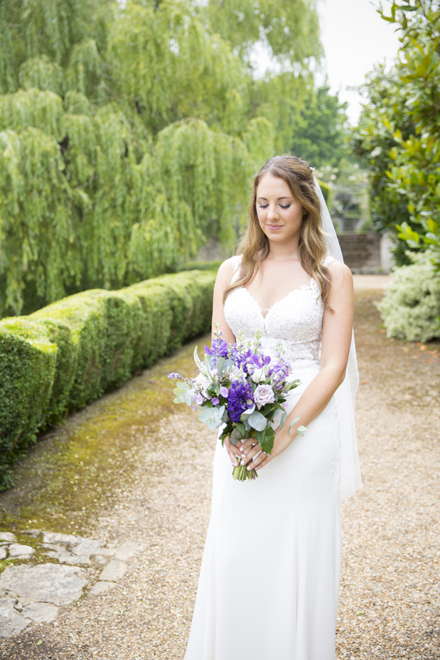 Bride looking down at purple bouquet at Nettlestead Place wedding in Maidstone, Kent. Captured by photographer, Victoria Green.