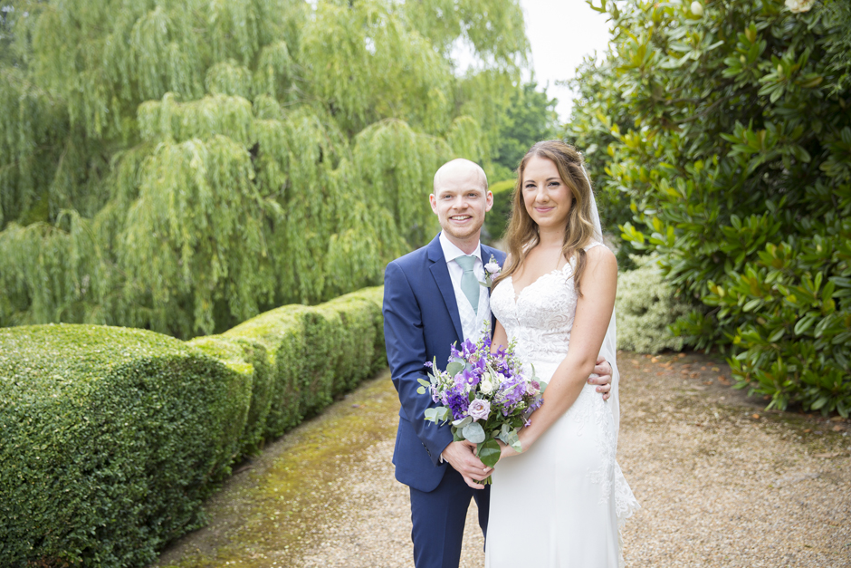 Bride and groom standing together at Nettlestead Place wedding in Kent.