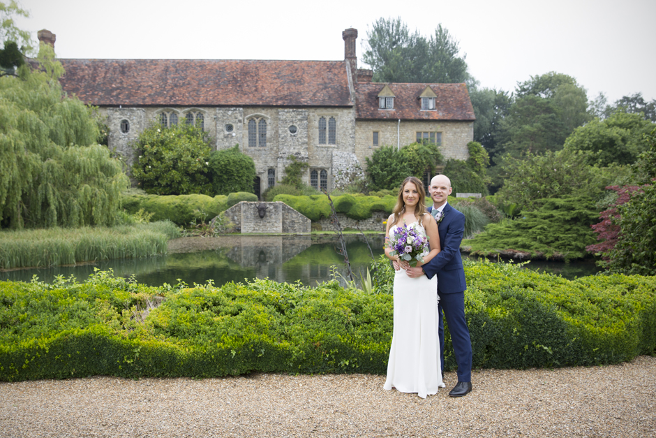 Bride and groom standing at Nettlestead Place wedding with house and lake in the background.