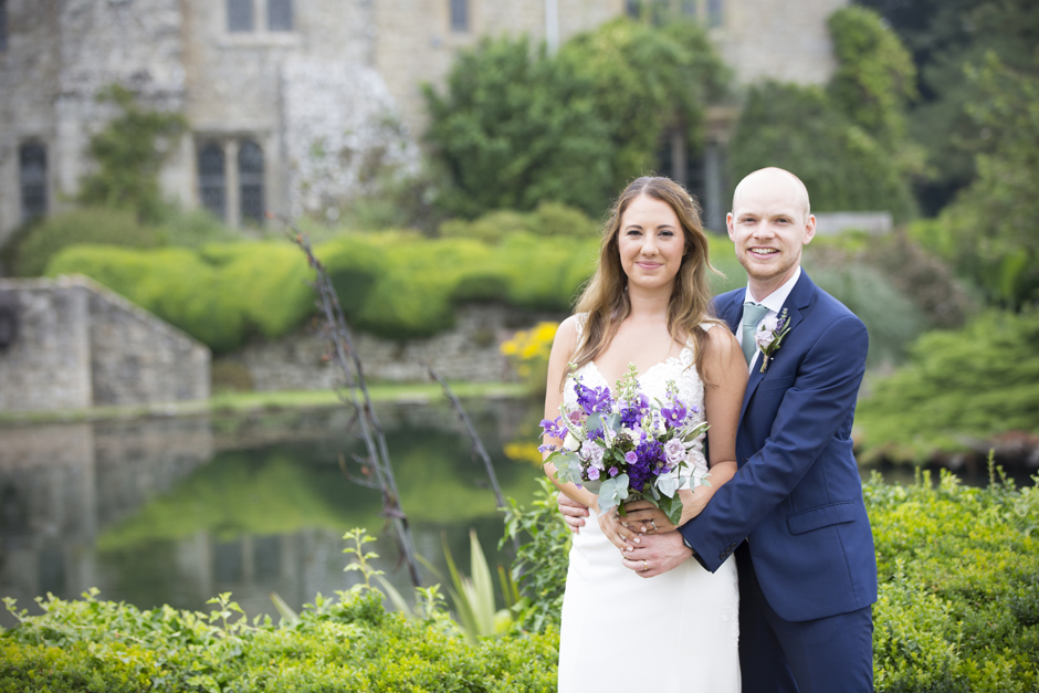 Bride and groom standing in front of lake at Nettlestead Place in Maidstone, Kent.