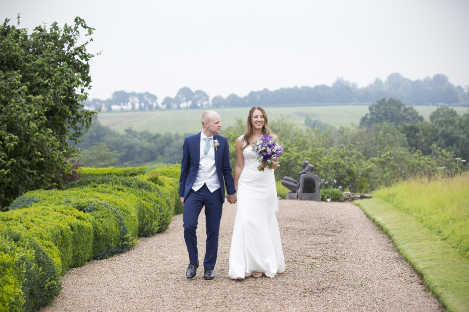 Bride and groom walking at Nettlestead Place wedding. Captured by Kent wedding photographer Victoria Green.