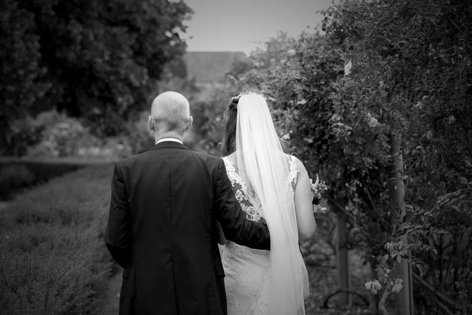 Close-up back of bride and groom walking through the rose gardens at Nettlestead Place wedding. Captured by photographer, Victoria Green.