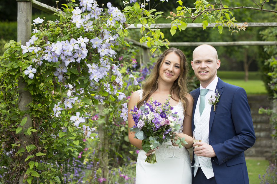 Bride and groom standing in the gardens at Nettlestead Place amongst some bright purple flowers. Captured by photographer Victoria Green.