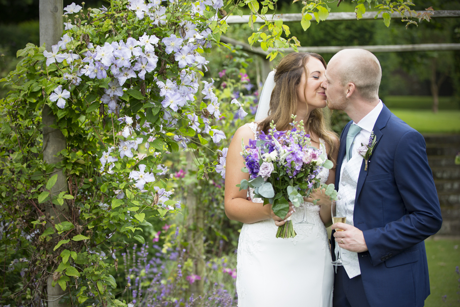 Bride and groom sharing an intimate kiss in flower gardens of Nettlestead Place in Kent. Captured by wedding photographer, Victoria Green.