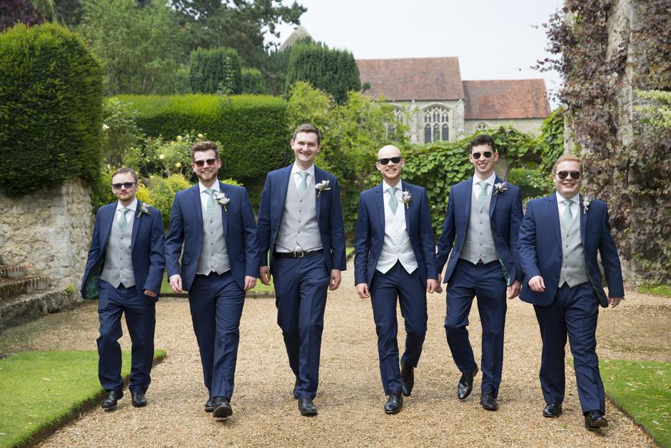 Groom and groomsmen walking at Nettlestead Place wedding. Captured by Kent wedding photographer, Victoria Green.