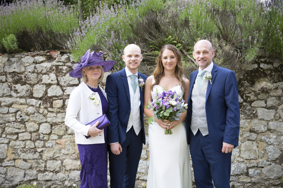 Bride and groom with groom's parents at Nettlestead Place wedding in Maidstone, Kent.