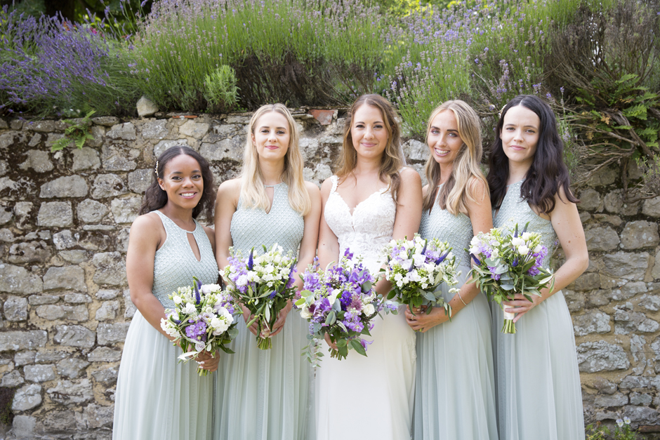 Bride standing with bridesmaids at Nettlestead Place wedding, in Kent. Captured by Kent wedding photographer, Victoria Green.