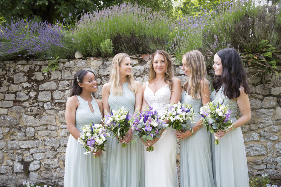 Bridesmaids looking at bride at Nettlestead Place wedding in Kent. Captured by Kent wedding photographer, Victoria Green.