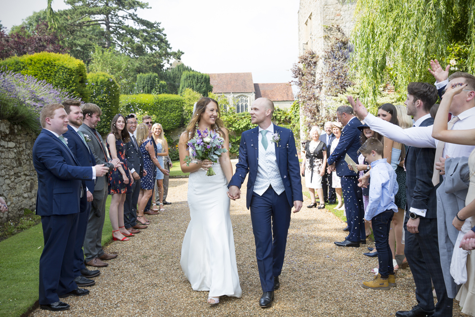 Bride and groom laughing as confetti is thrown on them at Nettlestead Place wedding in Maidstone, Kent.