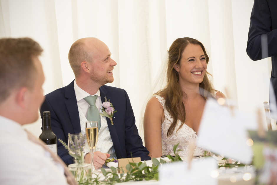 bride and groom laughing during speeches at Nettlestead Place wedding in Maidstone, Kent.