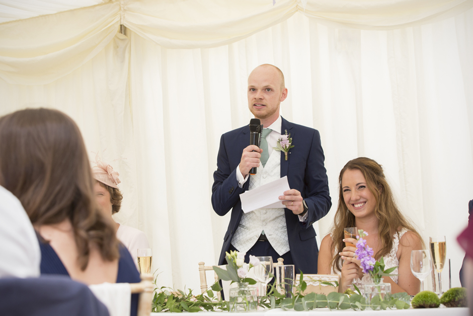 Groom saying speech with bride to his side laughing at Nettlestead Place in Maidstone.