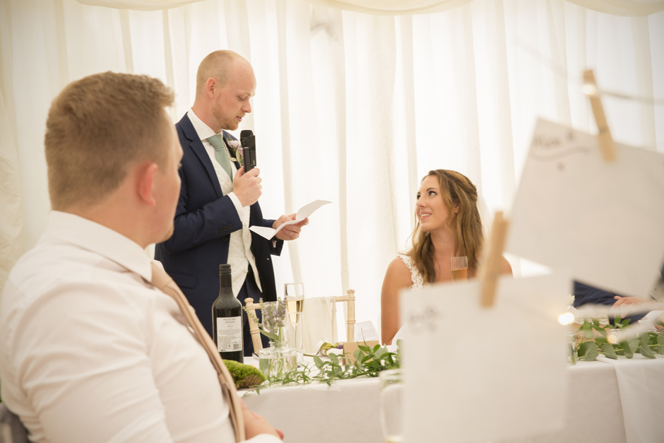 Wife listening attentively to groom's speech at Nettlestead Place in Maidstone, Kent.