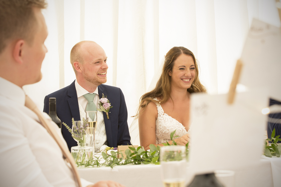 Bride and groom laughing at speeches at Nettlestead Place in Maidstone, Kent.
