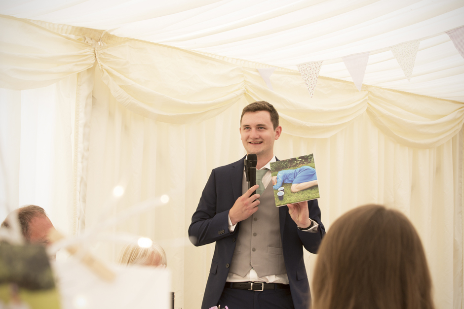 Bestman saying his speech holding canvas incriminating groom at Nettlestead Place in Maidstone, Kent.