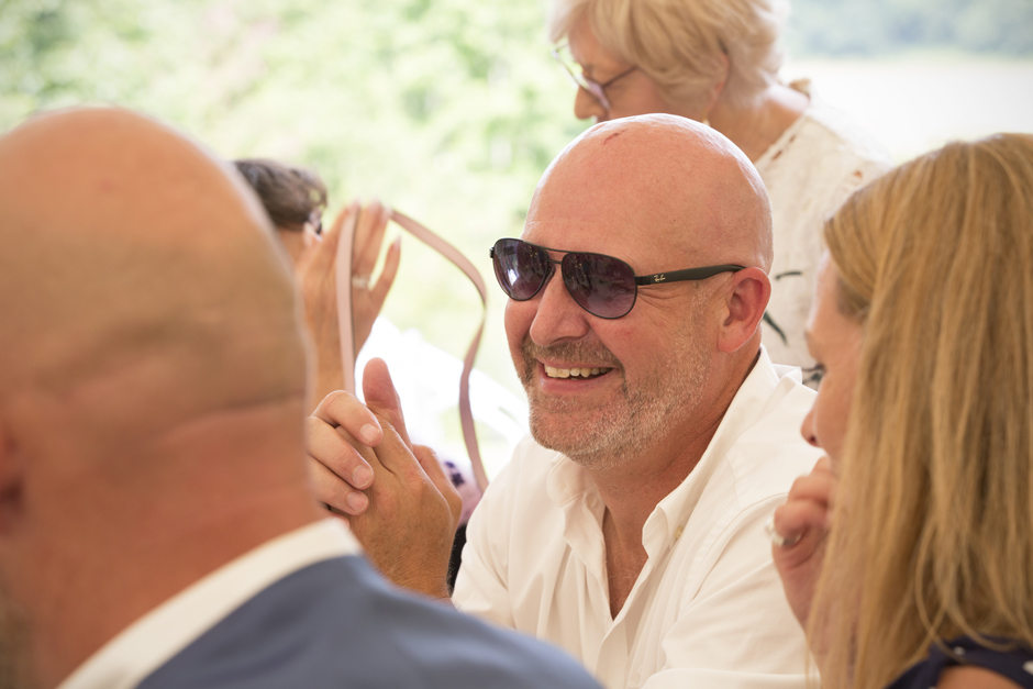Male wedding guest with sunglasses laughing during speeches at Nettlestead Place in Maidstone, Kent.