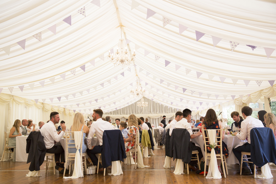 Wide shot showing the wedding marquee and guests sitting to eat at Nettlestead Place in Kent