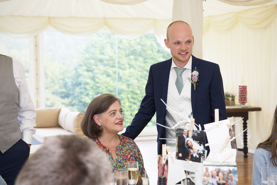 Groom chatting to guests at tables at Nettlestead Place wedding in Kent.