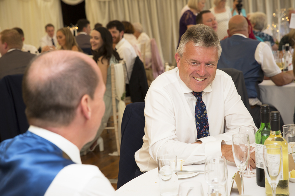 Male wedding guest smiling at another guest during evening wedding reception at Nettlestead Place in Maidstone, Kent.